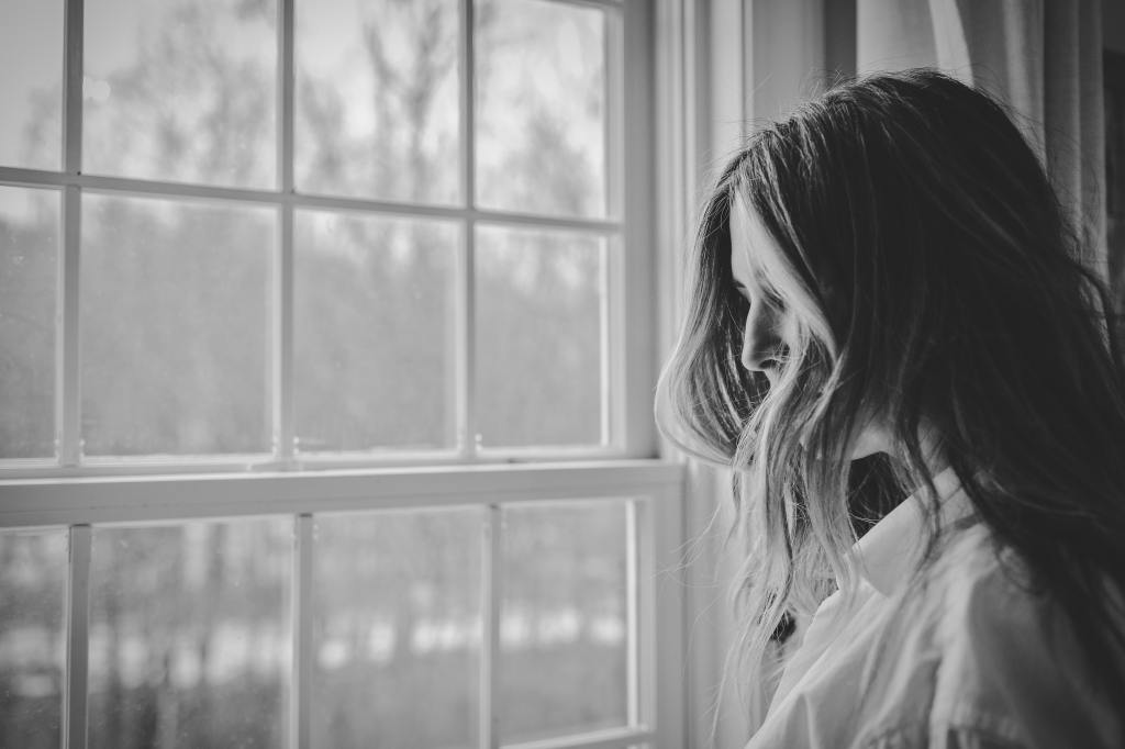 Woman standing near a window.