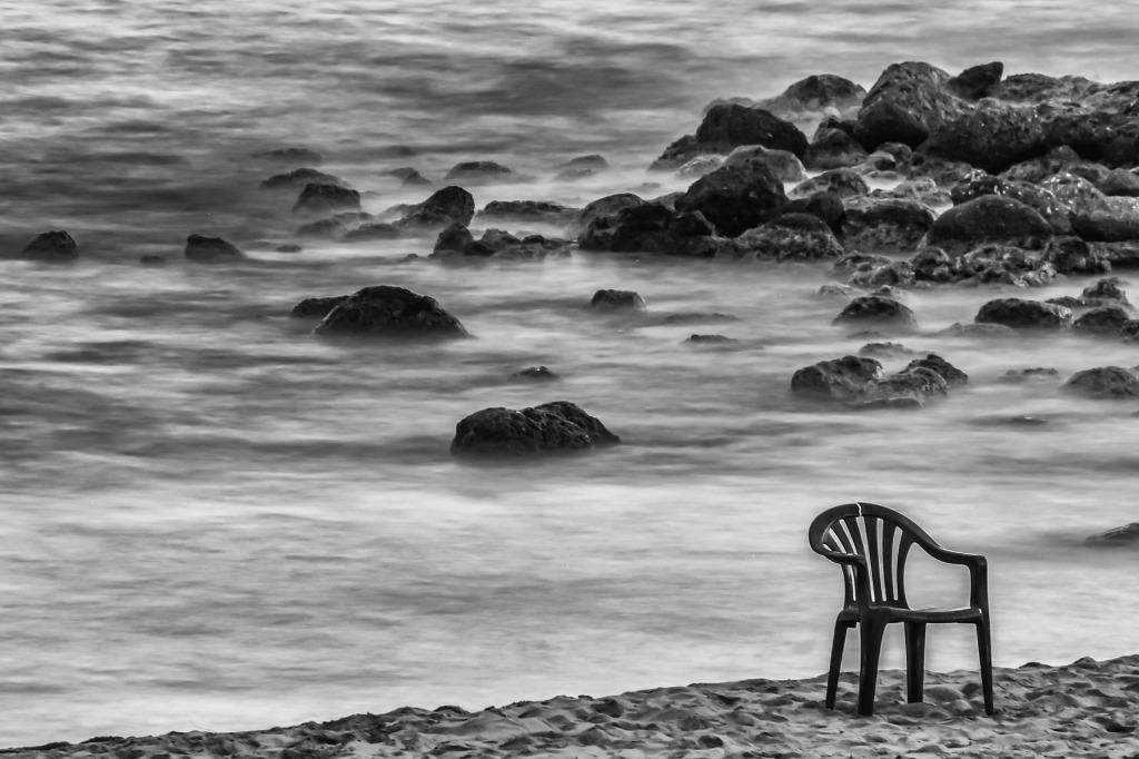 Broken chair on a sea shore.
