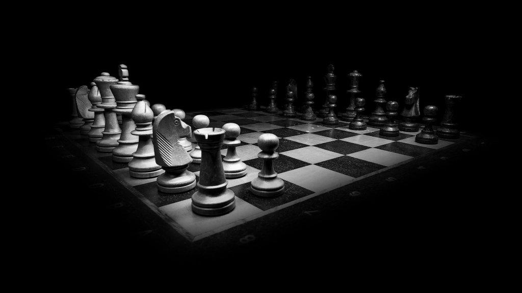Lit chessboard on a dark background.