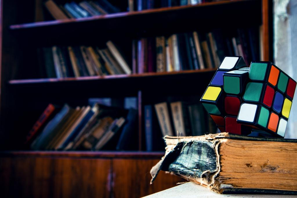 Rubik's cube on top of a worn out book.